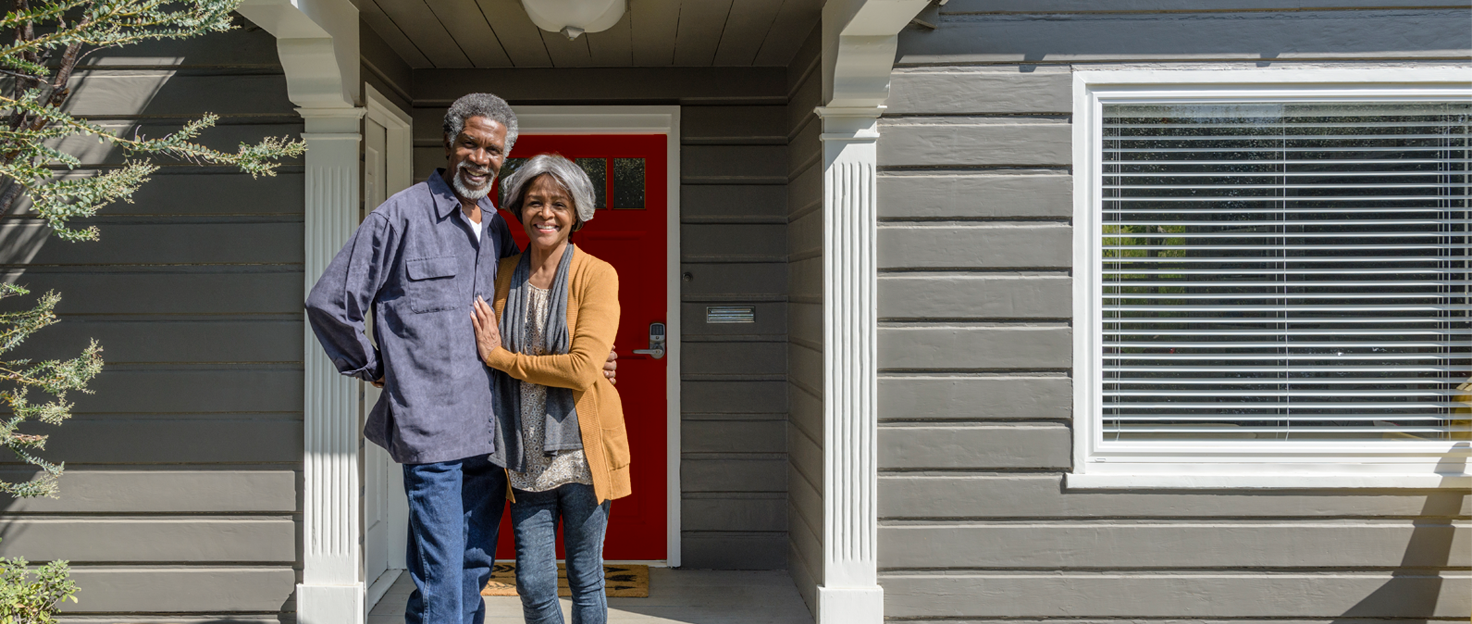 Mature couple on front porch in front of newly redesigned home