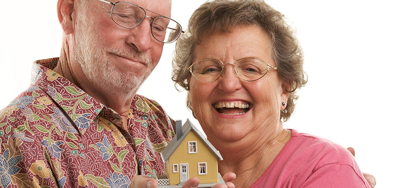 Mature Couple holding a miniature model of a home modification house