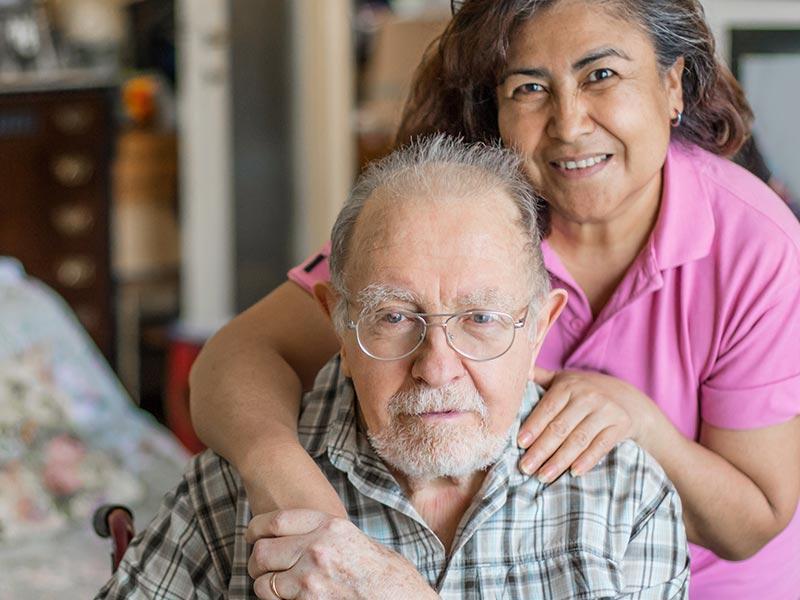 Caregiver with hands on older man's shoulders